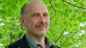 stock-footage-portrait-of-bald-headed-middle-aged-man-with-moustache-stands-under-tree